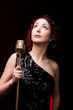 Attractive young woman vocalist with retro microphone musical pe. Beautiful young female singer in sparkling black evening dress with golden vintage microphone stock image