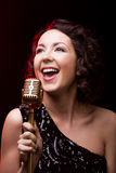 Attractive young woman vocalist singing with retro microphone Stock Photo