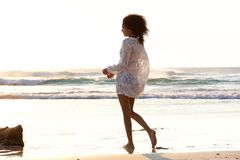 Attractive young woman walking on the beach barefoot Royalty Free Stock Photo