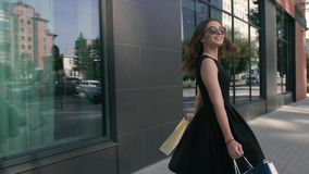 Attractive young woman walking downtown after shopping stock video footage