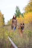 Attractive young woman walking with her dog German shepherd at autumn forest, near rail way - the girl is in focus Stock Image
