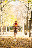Attractive young woman walking in the park in the autumn time holding colorful foliage Stock Photo