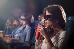 Attractive young woman watching a movie at the cinema. Movie mania. Shot of a beautiful young female in 3D glasses sipping her drink while watching a movie at Royalty Free Stock Image