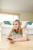 Attractive young woman watching TV. Lying on the floor at home royalty free stock photography