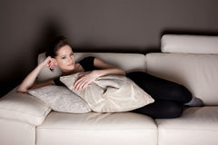 An attractive young woman watching TV Stock Image