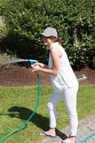 Attractive young woman watering the plants in the garden Royalty Free Stock Photography