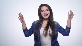 Attractive young woman waving her hands in the air with excitement and laughing