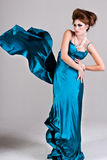 Attractive Young Woman Wearing a Blue Satin Dress. Attractive young woman standing with her hands on her hips in a blue satin, wind blown dress. Vertical shot Stock Photography