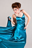 Attractive Young Woman Wearing a Blue Satin Dress. Attractive young woman standing in a blue satin dress that is being pulled to the side. Vertical shot Stock Photo