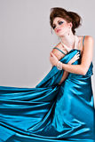 Attractive Young Woman Wearing a Blue Satin Dress. Attractive young woman standing in a blue satin dress that is being pulled to the side. Vertical shot Royalty Free Stock Photography