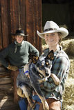 Attractive Young Woman Wearing a Cowboy Hat. And holding an Australian Shepherd. A young man is standing in the background. Vertical shot Royalty Free Stock Photo