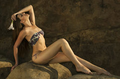 An attractive young woman wearing a designer's bikini seats in front of a rock Royalty Free Stock Image