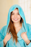 Attractive young woman wearing hooded blue bathrobe Royalty Free Stock Images