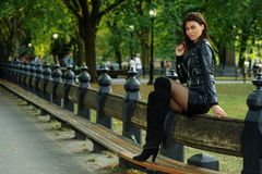 Attractive young woman wearing leather jacket, mini skirt and over-knee boots. Posing at the autumn park Royalty Free Stock Image