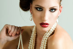 Attractive Young Woman Wearing Pearls. Attractive young woman wearing a pearl necklace and earrings. Horizontal shot Stock Photography