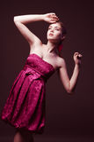 Attractive young woman wearing on pink dress. And looking upwards Stock Photography