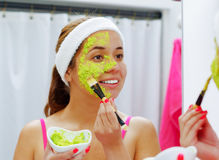 Attractive young woman wearing pink top and white headband, applying avocado mixture to face using brush, looking in Royalty Free Stock Photo