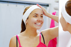 Attractive young woman wearing pink top and white headband facing mirror, smiling while touching forehead with hand Royalty Free Stock Photo