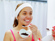 Attractive young woman wearing pink top and white headband, holding up bowl of dark chocolate, looking in mirror smiling Royalty Free Stock Photo