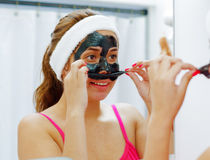Attractive young woman wearing pink top and white headband, removing black mask treatment from face using hands, looking Royalty Free Stock Photography