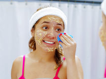 Attractive young woman wearing pink top and white headband, removing oat mixture from face using sponge, looking in Stock Photos