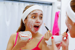 Attractive young woman wearing pink top and white headband using brush to apply cream on face, looking in mirror smiling Royalty Free Stock Images