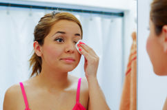 Attractive young woman wearing pink top and white headband, using cotton patch to clean around eye, looking in mirror Stock Photography