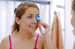 Attractive young woman wearing pink top and white headband, using eyelash curler tool on left eye, looking in mirror Stock Image