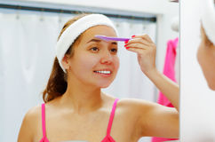 Attractive young woman wearing pink top and white headband, using skin cleaner on face looking in mirror smiling Stock Photos