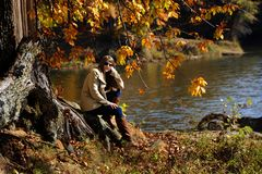 Autumn Contemplation on Poplar Tree Lake. Attractive young woman, wearing sunglasses, jeans, boots and coat, rests on the root of a large tree covered in orange stock image