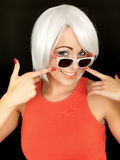 Attractive Young Woman Wearing Sunglasses Pointing to Her Smile Stock Image