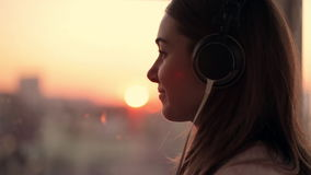 Attractive young woman wears listening to music on the smartphone at city blurred background with sunset. enjoying the stock video footage