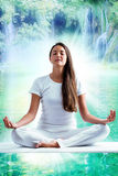 Attractive young woman in white meditating at lake. Stock Photo