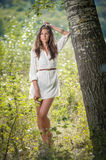 Attractive young woman in white short dress posing near a tree in a sunny summer day. Beautiful girl enjoying the nature Stock Photography