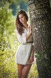 Attractive young woman in white short dress posing near a tree in a sunny summer day. Beautiful girl enjoying the nature. In a green forest. Portrait of sensual Royalty Free Stock Photography