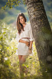 Attractive young woman in white short dress posing near a tree in a sunny summer day. Beautiful girl enjoying the nature Royalty Free Stock Images