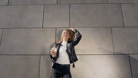 Attractive young woman in a white t-shirt and jacket holding milkshake while spin around herself at outdoor. Emotions. Lifestyle, beauty, people, food concept stock video