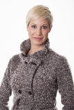 Attractive young woman in a winter coat. Elegant woman smiles with her jacket isolated on white background Stock Images