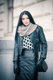 Attractive young woman in a winter fashion shot. Beautiful fashionable young girl in black leather on avenue Stock Photos