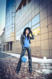 Attractive young woman in a winter fashion shot. Beautiful fashionable young girl in black leather with big hat and blue handbag. Posing in front of modern Royalty Free Stock Image