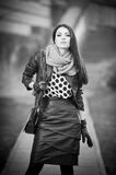 Attractive young woman in a winter fashion shot. Beautiful fashionable young girl in black leather outfit posing on avenue Royalty Free Stock Photos