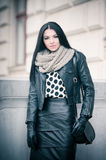 Attractive young woman in a winter fashion shot. Beautiful fashionable young girl in black leather outfit posing outdoor. Elegance. Attractive young woman in a Royalty Free Stock Images
