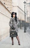 Attractive young woman in a winter fashion shot. Beautiful fashionable young girl in black  posing on avenue. Elegant brunette Royalty Free Stock Photography