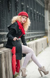 Attractive young woman in a winter fashion shot. Beautiful young girl with red umbrella in the street Stock Image