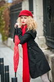 Attractive young woman in a winter fashion shot. Beautiful young girl with red umbrella in the street Stock Photography