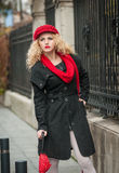 Attractive young woman in a winter fashion shot. Beautiful young girl with red umbrella in the street Stock Images