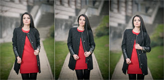 Attractive young woman in winter fashion shot with building on background. Beautiful fashionable girl in black coat over red dress Royalty Free Stock Photography