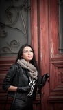 Attractive young woman in winter fashion shot with wrought iron decorated doors in background. Beautiful fashionable female Stock Photos