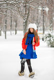 Attractive young woman in wintertime outdoor. The girl in colored clothing. Stock Photo
