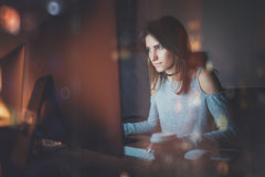 Attractive young woman working on coworking office at night. Girl using contemporary desktop computer, blurred. Background. Horizontal, film effect, reflections Stock Photos